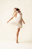 Attractive young woman dancing. Studio light background Royalty Free Stock Photos