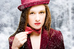 Attractive young woman in dark red jacket, hat and Royalty Free Stock Photo