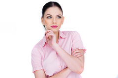 Attractive young woman deep in thought. Standing with her hand to her chin staring upwards with a slight frown as she tries to remember something, isolated on Royalty Free Stock Images
