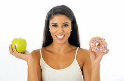 Attractive young woman on a diet deciding between an apple and a doughnut stock photo