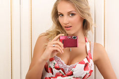 Attractive young woman with digital camera. Attractive young woman holding digital camera and looking at camera Stock Photo