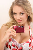 Attractive young woman with digital camera. Attractive young woman holding digital camera and looking at camera Royalty Free Stock Photography