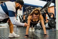 Attractive young woman does push-ups with trainer in gym. Young fit women doing push-ups exercise in modern gym with personal trainer stock photography