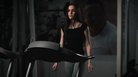 Attractive young woman doing cardio exercise on treadmill at gym. Dark space stock footage