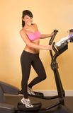 Attractive young woman doing cardio workout. Young woman working out on elliptical machine Stock Image