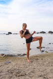 Attractive Young Woman Doing Exercise on the Beach Royalty Free Stock Image