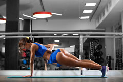 Attractive young woman is doing plank exercise while working out in gym Royalty Free Stock Image