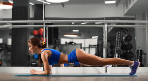 Attractive young woman is doing plank exercise while working out in gym Royalty Free Stock Photos