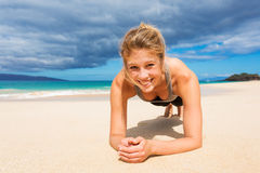 Attractive Young Woman Doing Push Up Exercise. On the Beach royalty free stock image