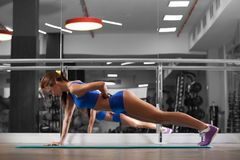 Attractive young woman is doing push ups exercise while working out in gym Royalty Free Stock Photography
