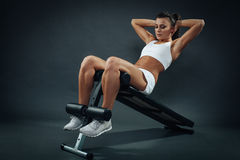 Attractive young woman doing sit ups on bench Stock Photos