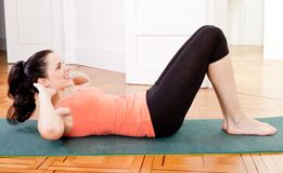 Attractive young woman doing sit ups. At home sport workout Royalty Free Stock Photos