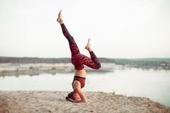 An attractive young woman doing a yoga pose for balance and stretching near the lake high in the mountains royalty free stock images