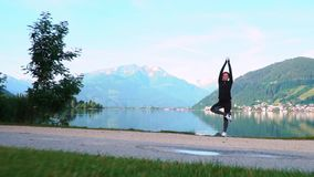 An attractive young woman doing a yoga pose for balance and stretching near the lake Zell am See high in the Alpine mountains in A