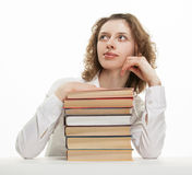 Attractive young woman dreaming. Leaned her elbows on stack of books Stock Photography