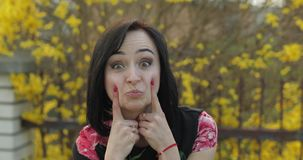 Attractive young woman in a dress with flowers making funny faces stock footage