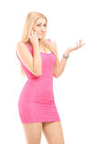 Attractive young woman in a dress using a cell phone Stock Photo