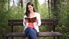 Attractive young woman with old book in the park. Slide slider. Attractive young woman dressed casually reads old book sitting on a wooden bench in the forest stock footage