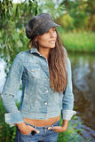 Attractive young woman dressed in jean and beret. Attractive young woman dressed in jean jacket and beret on the river coast stock photos