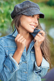 Attractive young woman dressed in jean and beret. Attractive young woman dressed in jean jacket and beret holding on herself jacket collar Stock Images