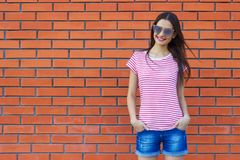 Attractive young woman dressed in a red and white striped t-shirt posing on a background of a red brick wall royalty free stock photography