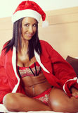 Attractive young woman dressed in santa claus. Attractive young woman dressed in Christmas sitting on a bed Stock Photo