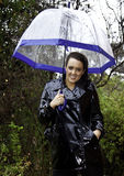 Attractive young woman dressed for wet weather. In shiny black raincoat and umbrella Stock Photography