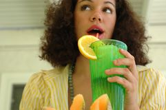 Attractive young woman drinkin Stock Photos