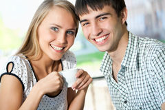 Attractive young woman drinking coffee with her boyfriend stock photography