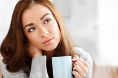 Attractive young woman drinking coffee at home. Attractive young woman drinking coffee Stock Photography