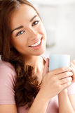 Attractive young woman drinking coffee at home. Portrait of an attractive young woman smiling staring Stock Photo