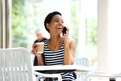 Attractive young woman drinking coffee and talking on mobile phone Royalty Free Stock Image