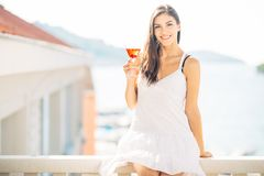 Attractive young woman drinking fruit alcoholic cocktail and enjoying her summer vacation.Holding glass of cold refreshing drink stock images