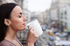 Attractive young woman is drinking hot beverage. Beautiful girl is enjoying a cup of coffee outdoors. She is standing on balcony and smelling the aroma. Her eyes Royalty Free Stock Image