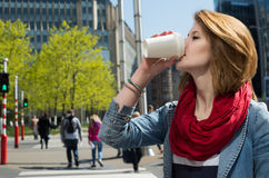 Attractive young woman drinking a hot drink from a paper cup Stock Photo