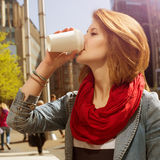 Attractive young woman drinking a hot drink from a paper cup. Attractive young woman enjoying a hot drink in a white paper cup against cityscape background Stock Images