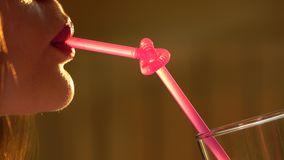 Attractive young woman drinking through knotted pink straw. 4K close-up video stock footage