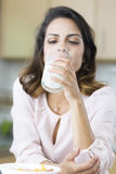 Attractive young woman drinking milk Stock Image