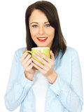 Attractive Young Woman Drinking a Mug of Coffee. Attractive Twenty Something Young Woman Drinking Coffee Royalty Free Stock Photo