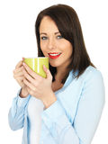 Attractive Young Woman Drinking a Mug of Coffee. Attractive Twenty Something Young Woman Drinking Coffee Royalty Free Stock Images