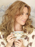 Attractive Young Woman Drinking Tea in Bed Stock Images