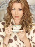 Attractive Young Woman Drinking Tea in Bed Royalty Free Stock Images