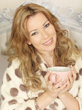Attractive Young Woman Drinking Tea in Bed Smiling Royalty Free Stock Photo
