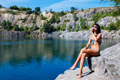 Attractive young woman drinking water sitting on a rocks outdoor Stock Photo