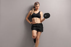 Attractive young woman with a dumbbell. Leaning against a gray wall Royalty Free Stock Photo