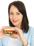 Attractive Young Woman Eating a Beef Burger Royalty Free Stock Images