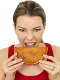 Attractive Young Woman Eating a Cooked Cornish Pasty Snack Royalty Free Stock Photography