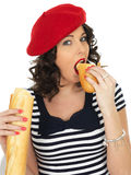 Attractive Young Woman Eating a French Stick Bread Loaf Stock Photos