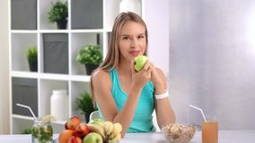 Attractive young woman eating fresh green apple in kitchen at home