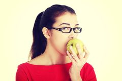 Attractive young woman eating green apple. Stock Photography